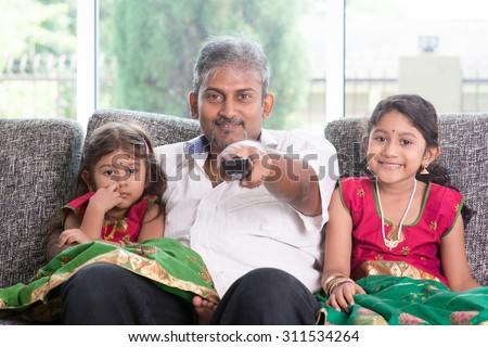 Happy Indian family watching tv together, father and children indoor living lifestyle at home. - stock photo