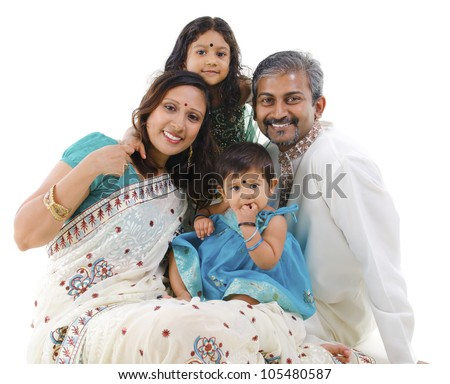 Happy Indian family with two children in traditional costume sitting on white background