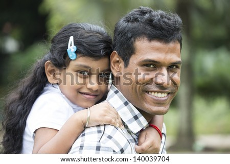 Happy Indian Father and daughter playing in the park. Lifestyle image. - stock photo