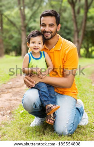happy indian father and son outdoors in forest - stock photo