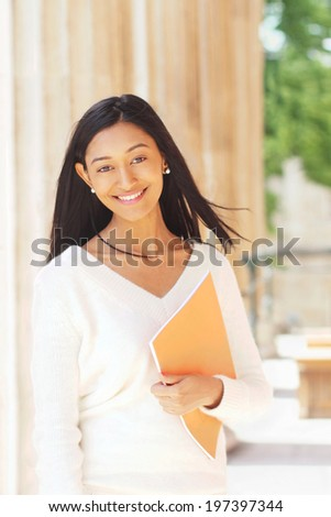 Happy indian female student holding a book with a columns at the background