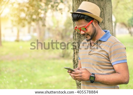 Happy indian guy looking his mobile phone and smiling - Young asian man texting online in park outdoor - New technology trends addiction concept - Warm filter with focus on face - stock photo