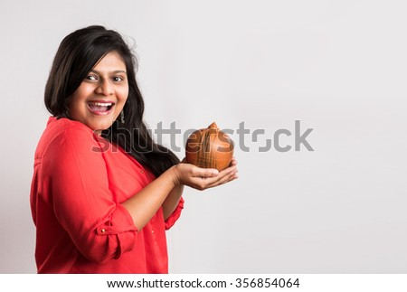 happy indian lady holding a piggy bank or clay money box, asian happy girl holding piggy bank or clay money box, isolated on white background  - stock photo