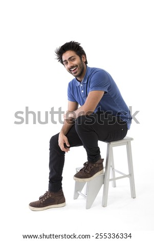 Happy Indian man sitting on a chair. Isolated on white - stock photo