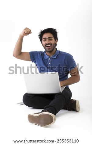 Happy Indian man using a laptop PC and cheering. Isolated on White Background. - stock photo