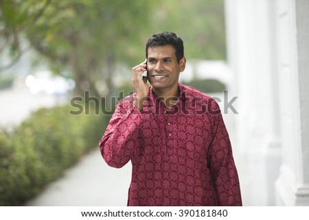 Happy Indian man using a smart phone on street. Traditional indian male wearing a kurta with smart phone outside. - stock photo
