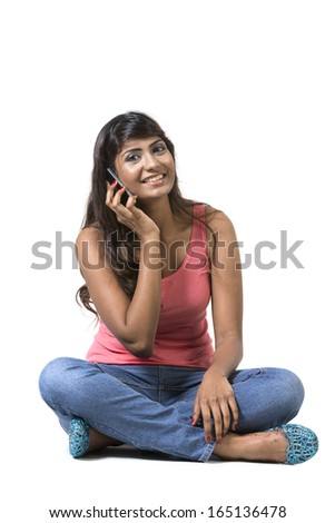 Happy Indian Woman using a smartphone. Isolated over a white background