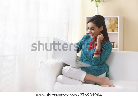 Happy Indian woman using laptop on sofa - stock photo