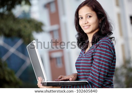 Happy Indian woman working with laptop outdoors - stock photo