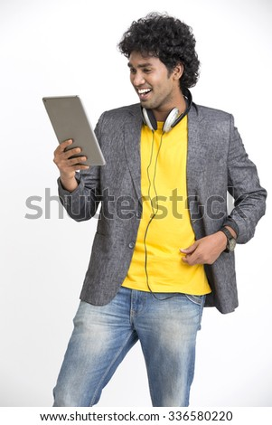 Happy Indian young man in headphones holding digital tablet on white background. - stock photo