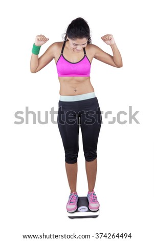 Happy indian young woman standing on weight scales while wearing sportswear and celebrate her success to weight loss - stock photo