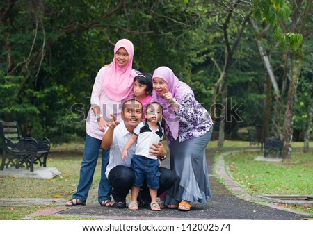 Happy indonesian Family enjoying family time together in the park - stock photo
