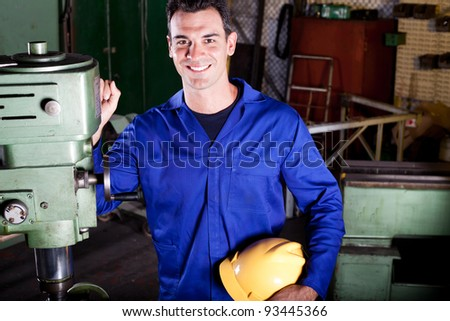 happy industrial craftsman portrait next to machine tool - stock photo