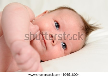 Happy Infant. Infant boy laying on his side with his hand on his chin. - stock photo