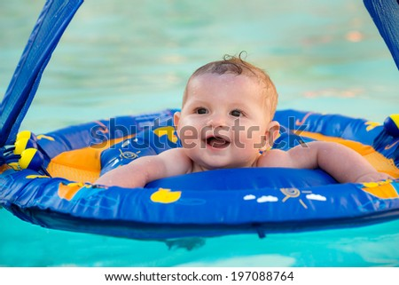 Happy infant playing in pool while sitting in baby float with canopy