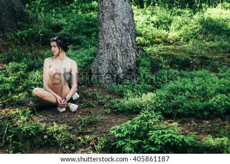 happy innocent woman sitting in green atmospheric forest on background of  mountains in summer