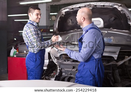 Happy insurance agent and professional mechanic indoors in workshop are examining a car after incident for front end damage and calculating loss
