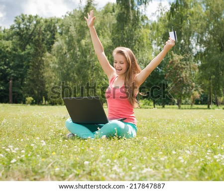 Happy internet shopping woman online with laptop and credit card sitting outdoor on green grass. Internet shopper buying things on the internet.