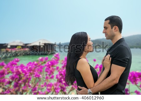 Happy interracial couple in love at sea side with bungalow background .Summer holidays,vacation, travel and dating concept. Asian woman,Caucasian man - stock photo