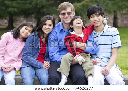 Happy interracial family enjoying day at park with disabled son - stock photo