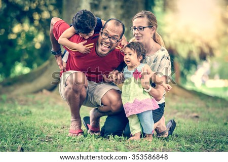 Happy interracial family is active and enjoying a day in the park. Little mulatto baby girl and boy. Successful adoption. Diverse family in nature with sun in the back. Healthy lifestyle. - stock photo
