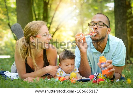 Happy interracial family is blowing bubbles. Happy interracial family is enjoying a day in the park. Mother father and mulatto son are smiling and are picnicking in the green park.