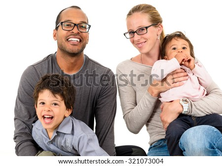 Happy interracial family is celebrating, laughing and having fun with Hispanic African American Father, Caucasian mother and Mulatto children son and daughter.  Isolated on white. - stock photo