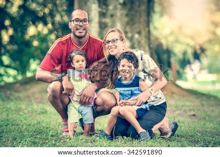 Happy interracial family is enjoying a day in the park. Little mulatto baby girl and boy. Successful adoption. Diverse family in nature with sun in the back. - stock photo