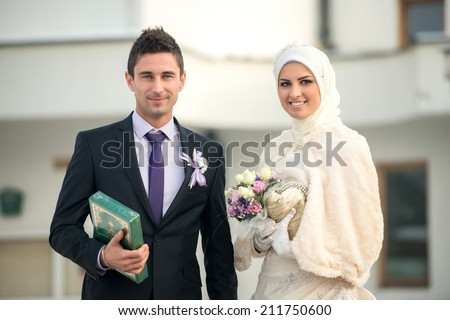 Happy islamic couple posing in front of mosque - stock photo