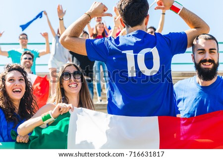 Happy Italian fans at stadium for soccer match. Group of supporters watching a sport match and cheering team Italy. Sport and lifestyle concepts.