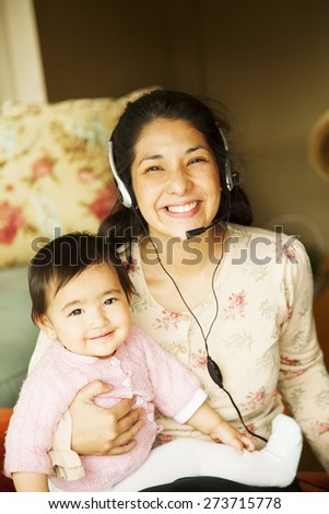 Happy japanese woman working with baby - stock photo