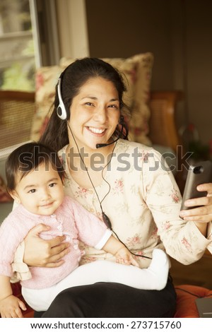Happy japanese woman working with baby, sending text message - stock photo