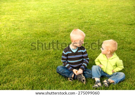 Happy joyful beautiful children (two little caucasian blond boys, brothers) sitting on green grass and having fun outdoor, sunny summer day, copy space, horizontal. - stock photo