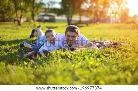 Happy joyful father and son having fun lying on the grass in summer sunny evening. Sunlight on the sunset - stock photo
