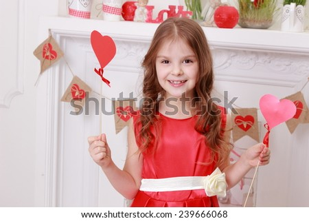 Happy joyful little girl holding red heart laughing and having fun - stock photo