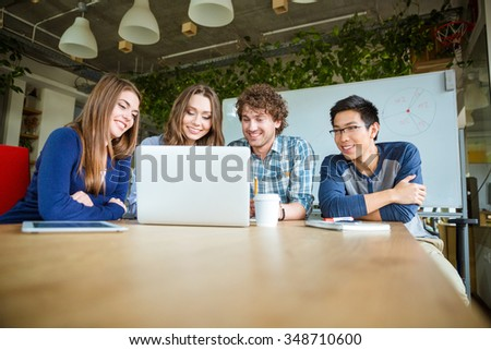Happy joyful students sitting in classroom and using laptop - stock photo