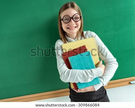 Happy joyful teen girl holding books / photo of teen school girl wearing glasses, creative concept with Back to school theme - stock photo
