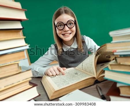 Happy joyful teenage girl reading a book / photo of teen school girl wearing glasses, creative concept with Back to school theme - stock photo
