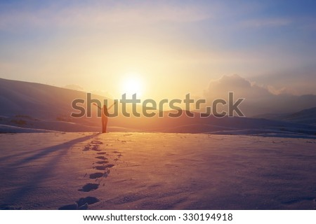 Happy joyful woman having fun outdoors in winter, standing on the mountains with raised up hands on the mountain covered with snow, enjoying beautiful sunset - stock photo