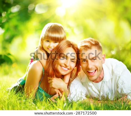 Happy joyful young family father, mother and little daughter having fun outdoors, playing together in summer park. Mom, Dad and kid laughing, lying on green grass, enjoying nature outside. Sunny day - stock photo