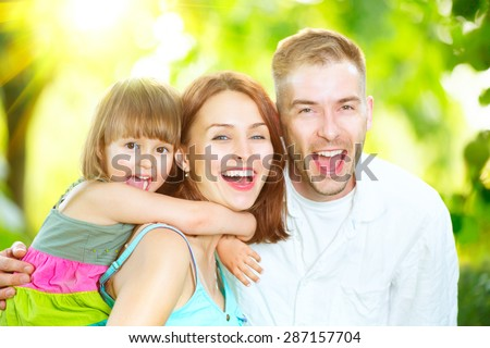 Happy joyful young family father, mother and little son having fun outdoors, playing together in summer park, countryside. Mom, Dad and kid laughing and hugging, enjoying nature outside. Sunny day - stock photo