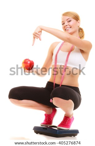 Happy joyful young woman girl with measuring tape on weighing scale holding apple. Slimming and dieting. Healthy lifestyle nutrition concept. Isolated on white background. - stock photo
