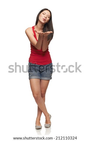 Happy joyfulwoman in full length blowing on palms, blowing a kiss to you, over white background - stock photo