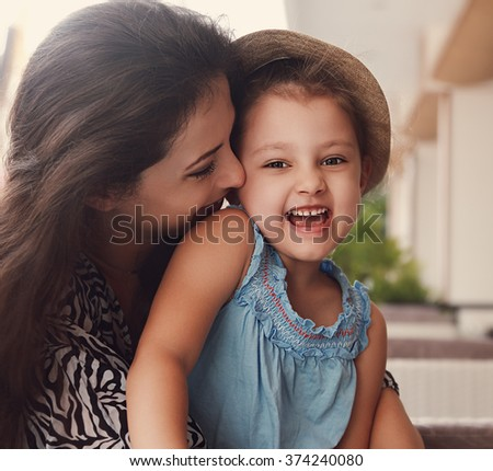 Happy joying kid girl embracing with beautiful mother on summer background. Closeup toned portrait of love emotion family
