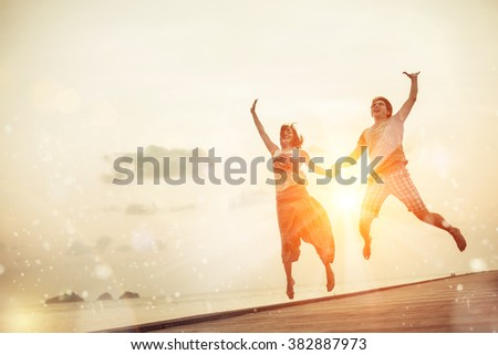 Happy jumping couple on the tropical sunset background.