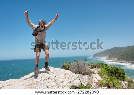 Happy jumping old man against beach background. Shot on the Otter trail in the Tsitsikamma National Park, Garden Route area, Western Cape, South Africa.  - stock photo