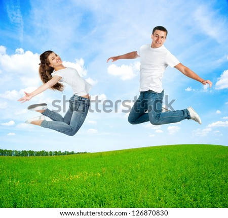 happy jumping young people jump on a summer day - stock photo
