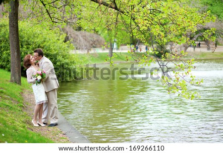 Happy just married couple hugging and kissing in park