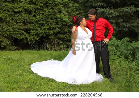 Happy just married multiracial modern couple with piercings, tattoos, and dreadlocks wearing matching colors of red and black