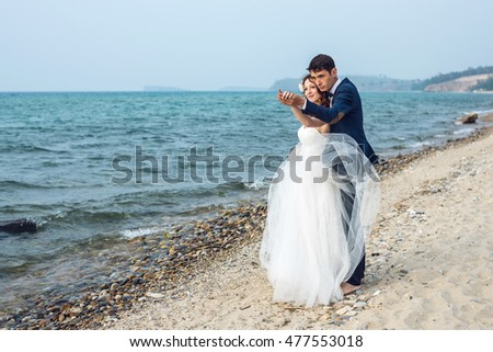 happy just married young couple celebrating at beautiful beach on Olkhon island